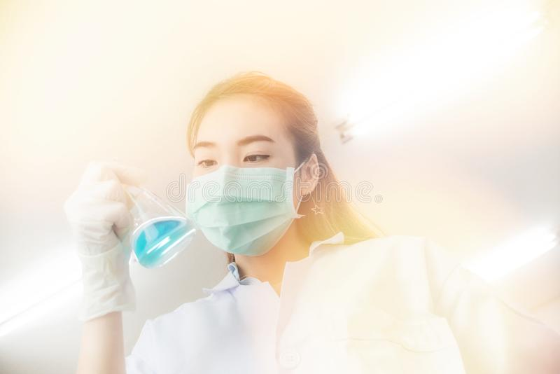 Young Asian scientist with test tube making research in clinical laboratory.Science, chemistry, technology, biology and people con. Pipette dropping a sample in stock photos