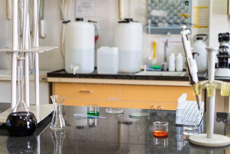 Pipette et solutions liquides chimiques colorées dans des flacons sur le plan de travail de laboratoire image libre de droits