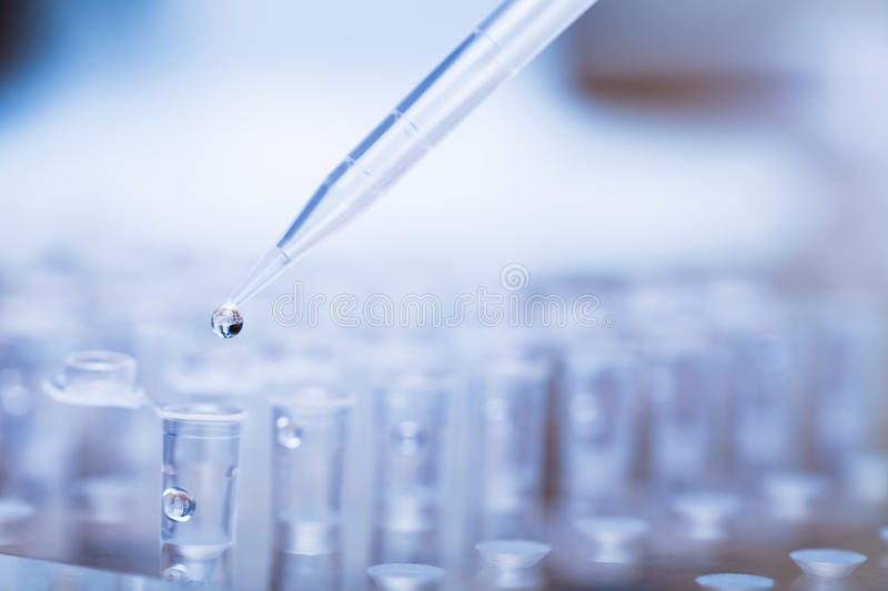 Pipette tip with droplet over rack of test tubes stock images