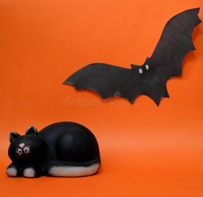 Pipistrello di carta e un gatto della figurina su un fondo arancio fotografia stock libera da diritti