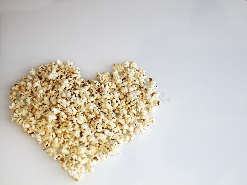 Pipoca apresentada na forma de um coração em um fundo branco fotos de stock