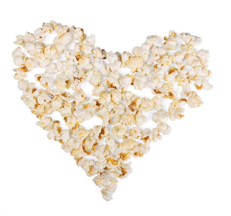 Pipoca, apresentada na forma do coração no fundo branco fotografia de stock