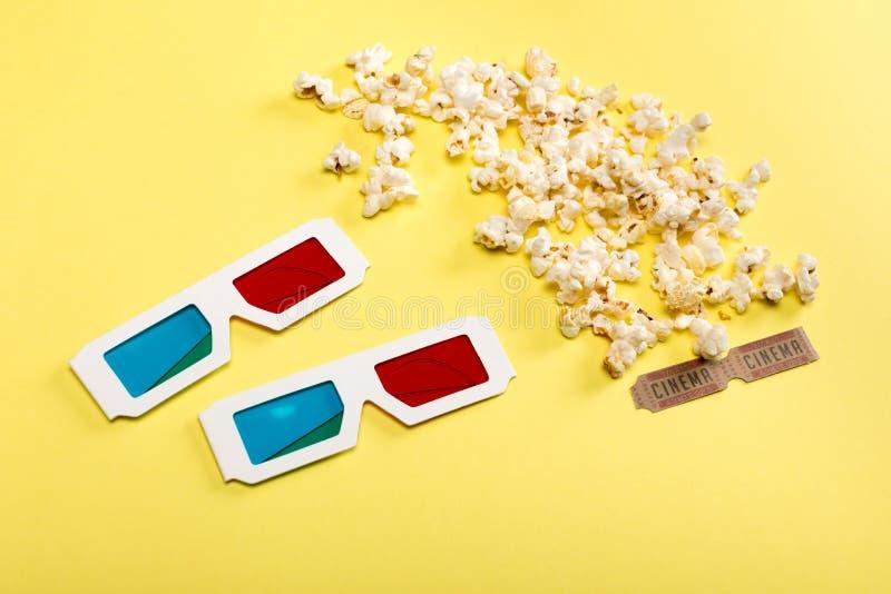 Pipoca, bilhetes do cinema e vidros 3D no amarelo, conceito do tempo de filme foto de stock