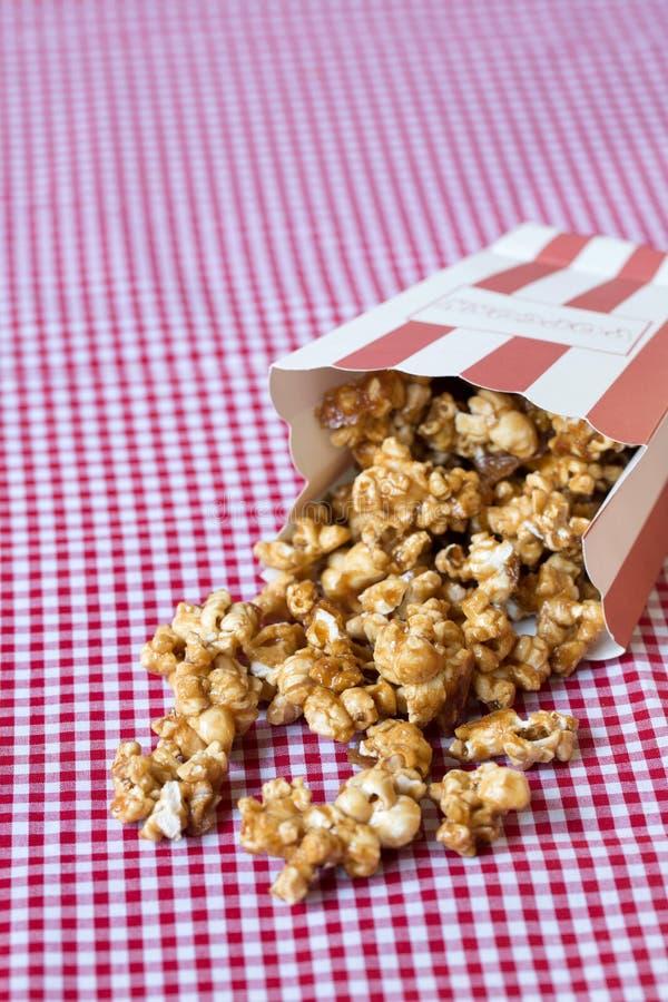 Pipoca do caramelo na toalha de mesa vermelha e branca fotografia de stock royalty free