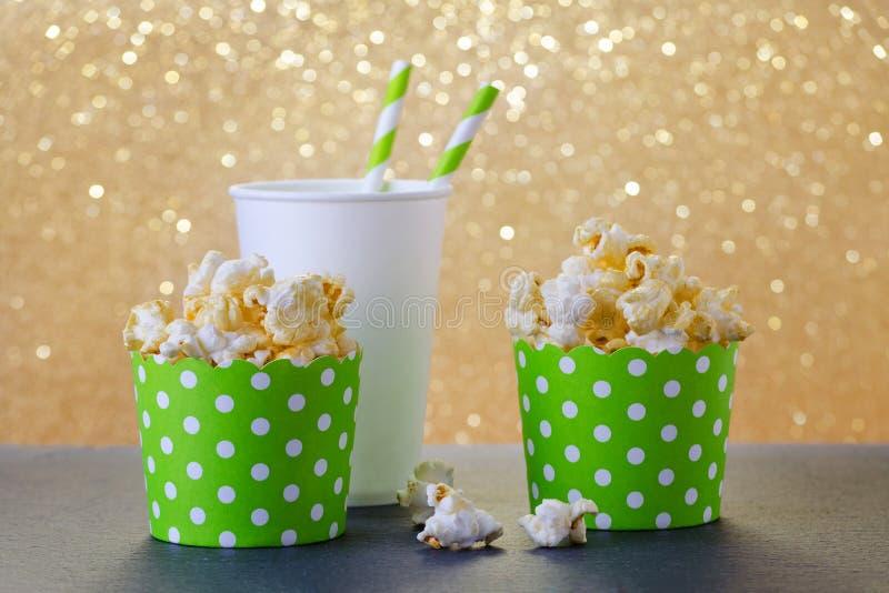 Pipoca e bebida no copo de papel para o filme e o entretenimento, fundo do bokeh do ouro fotos de stock royalty free
