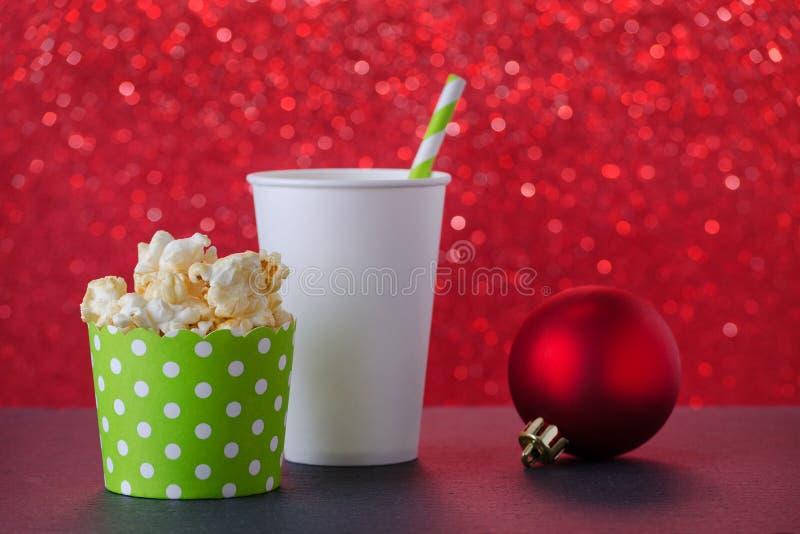 Pipoca e bebida no copo de papel para o filme e o entretenimento, fundo vermelho do bokeh, foco seletivo foto de stock royalty free