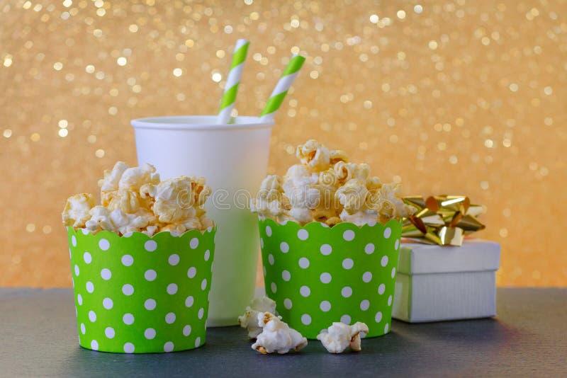 Pipoca e bebida no copo de papel para o filme e o entretenimento, um presente, fundo do bokeh do ouro foto de stock royalty free