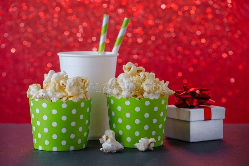 Pipoca e bebida no copo de papel para o filme e o entretenimento, um presente, fundo vermelho do bokeh foto de stock
