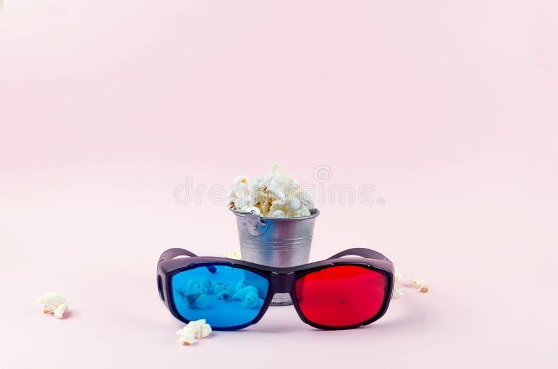 pipoca em uma cubeta e nos vidros 3D no rosa fotos de stock royalty free