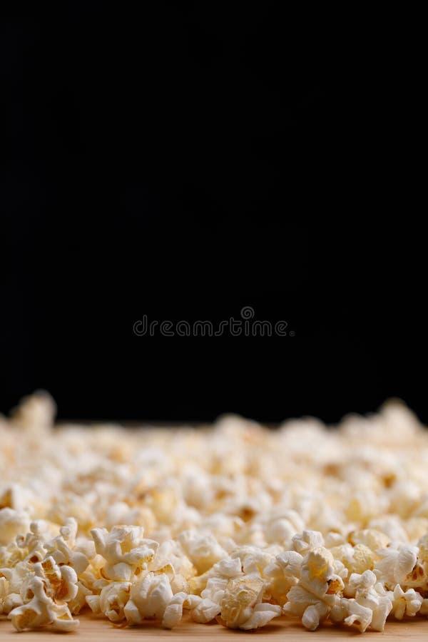 Pipoca salgada no close-up da tabela em um fundo preto Oscar Film Academy Concept Petiscos para olhar o filme imagem de stock royalty free