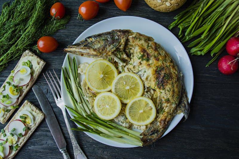 Pique cozido no forno, decorado com vegetais e ervas Servir em uma placa Nutri??o apropriada Fundo de madeira escuro imagem de stock