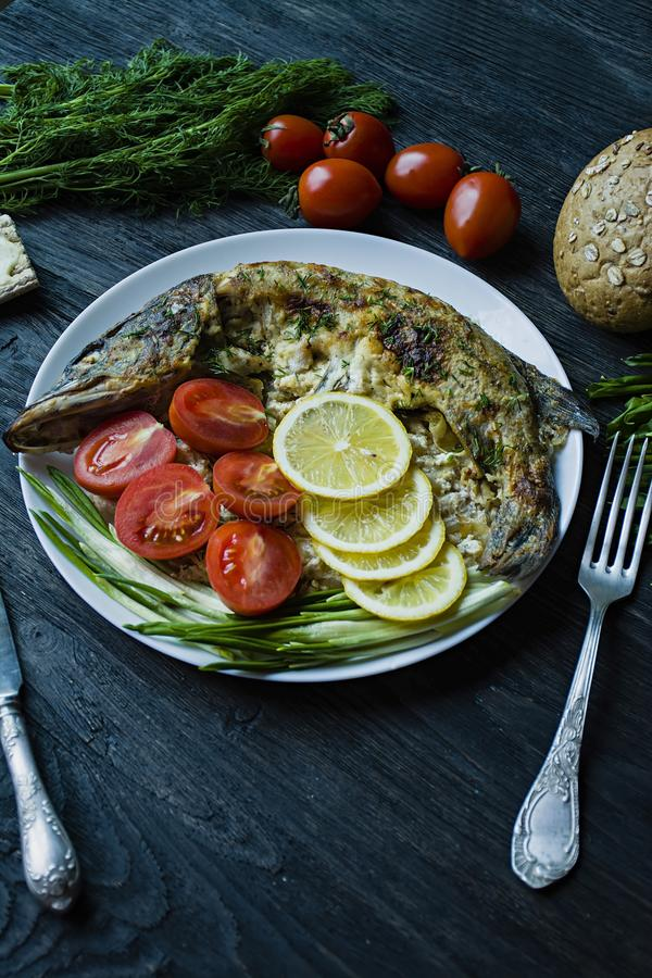 Pique cozido no forno, decorado com vegetais e ervas Servir em uma placa Nutri??o apropriada Fundo de madeira escuro foto de stock