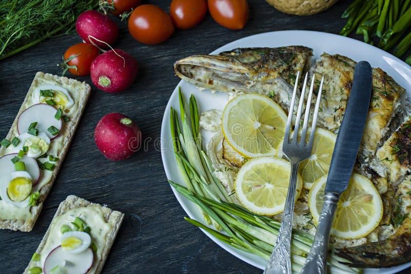 Pique cozido no forno, decorado com vegetais e ervas Servir em uma placa Nutri??o apropriada Fundo de madeira escuro fotografia de stock