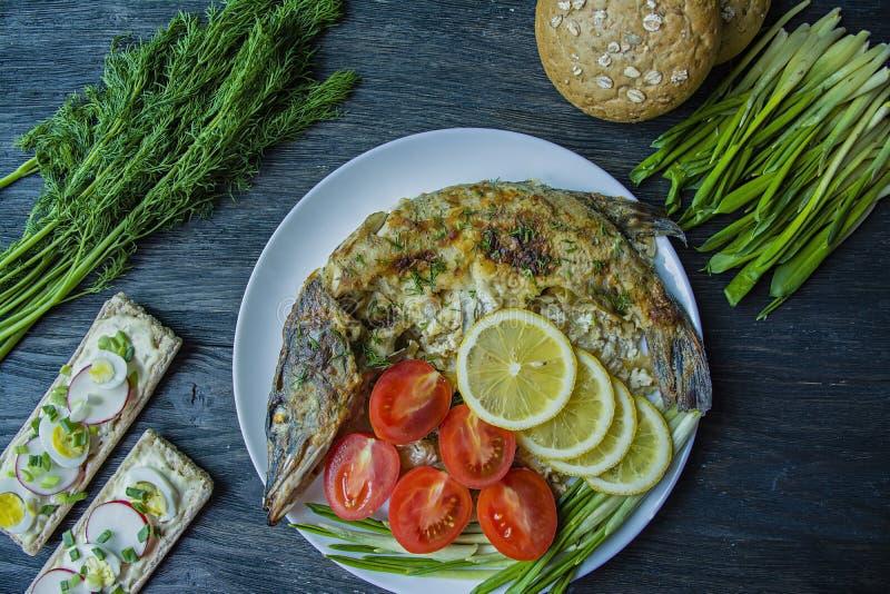 Pique cozido no forno, decorado com vegetais e ervas Servir em uma placa Nutri??o apropriada Fundo de madeira escuro foto de stock royalty free