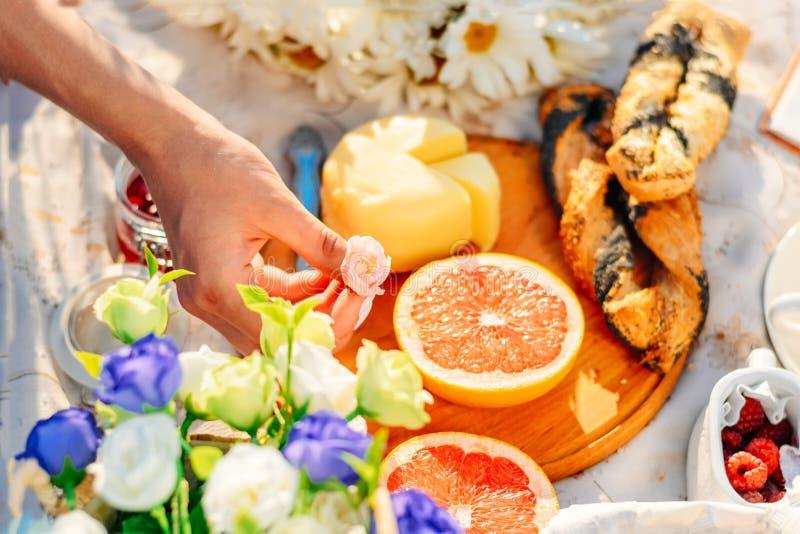 Pique-nique au coucher du soleil Fruits, fromage croissants sur la nappe rose de rose de prise de main du ` s de femme photos stock