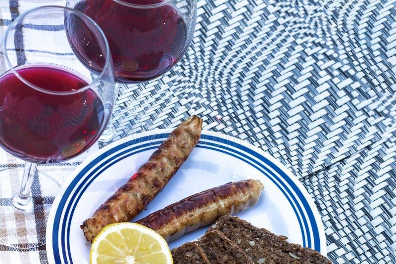 Pique-nique, barbecue en nature Vin rouge, saucisses grillées, légumes et pain sur une belle nappe photos libres de droits