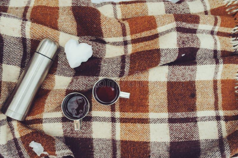 Pique-nique d'hiver sur la neige Coeur chaud de thé, de thermos et de boule de neige sur la couverture chaude confortable images stock