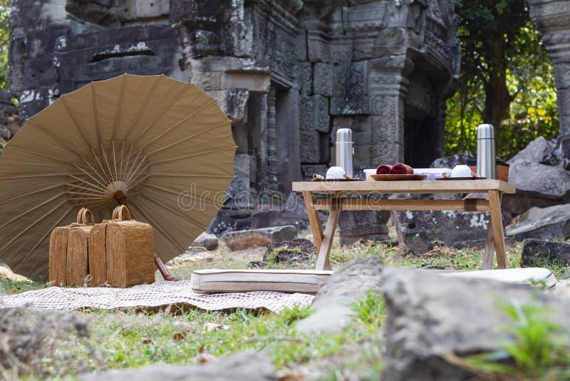 Pique-nique de style japonais près de temple antique de complexe d'Angkor Vat, Cambodge Idée de pique-nique avec le parapluie et  photo libre de droits