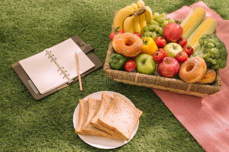 Pique-niquez au parc sur l'herbe avec la nourriture et buvez sur la couverture photographie stock