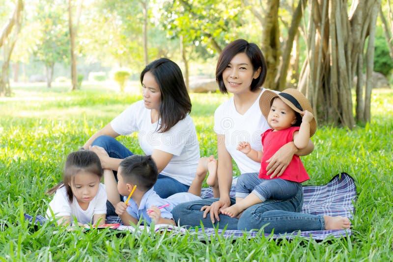 Piquenique asiático novo bonito do retrato da família do pai no parque, na criança ou nas crianças e no amor de mãe feliz e alegr imagens de stock