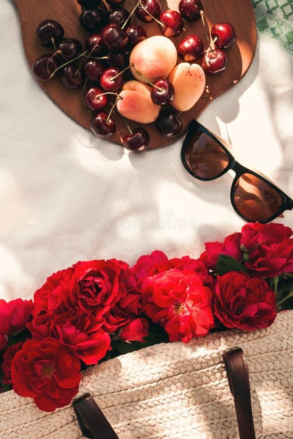 Piquenique do verão no jardim com as rosas vermelhas do jardim em um saco de vime, em óculos de sol e em bagas da cereja em uma c fotografia de stock