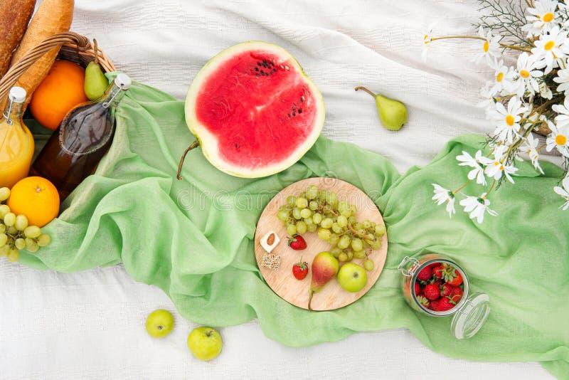 Piquenique do verão no prado na grama verde Cesta de fruto, suco e vinho engarrafado, melancia, morangos na imagem de stock
