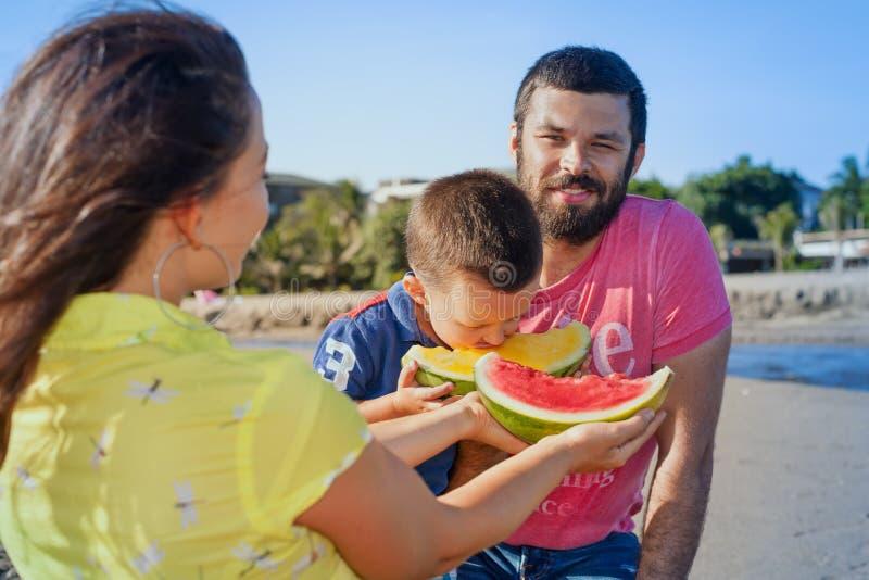 Piquenique engraçado da família feliz bonita na praia do mar da areia fotos de stock