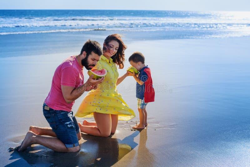 Piquenique engraçado da família feliz na praia da areia com ressaca do mar fotos de stock royalty free
