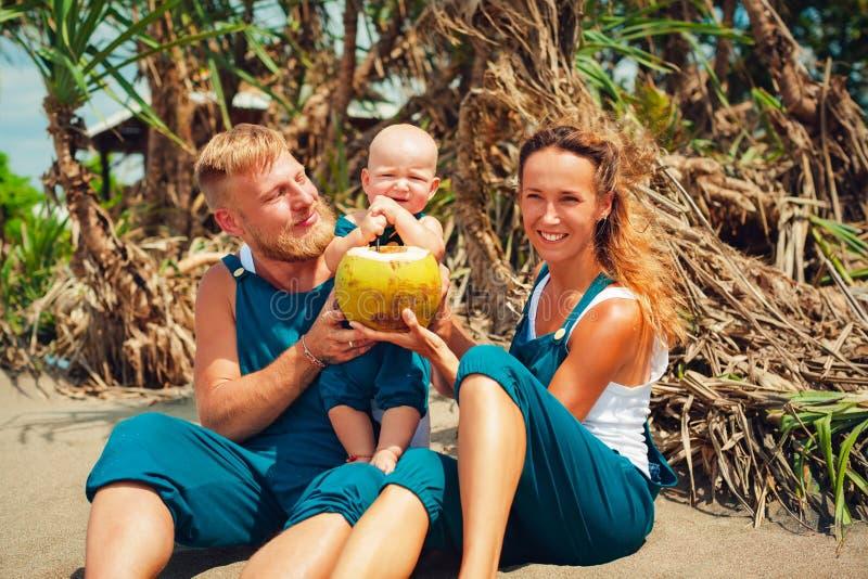 Piquenique feliz da família na praia Mãe, bebê da alimentação do pai fotos de stock royalty free