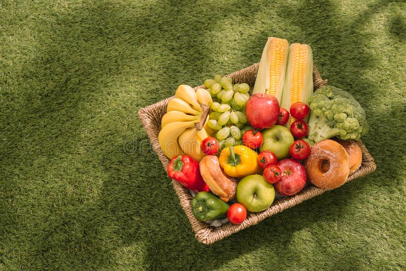Piquenique na grama Toalha de mesa verificada vermelha, cesta, alimento saudável e fruto, suco de laranja Vista superior Configur foto de stock