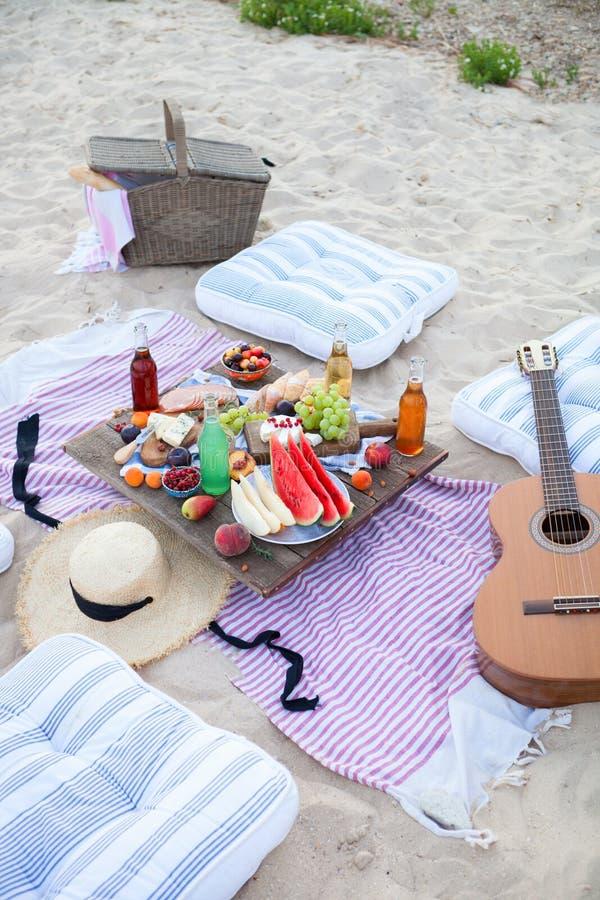 Piquenique na praia no por do sol no boho do estilo, no alimento e na concepção da bebida fotografia de stock