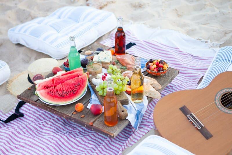 Piquenique na praia no por do sol no boho do estilo, no alimento e na concepção da bebida imagem de stock royalty free