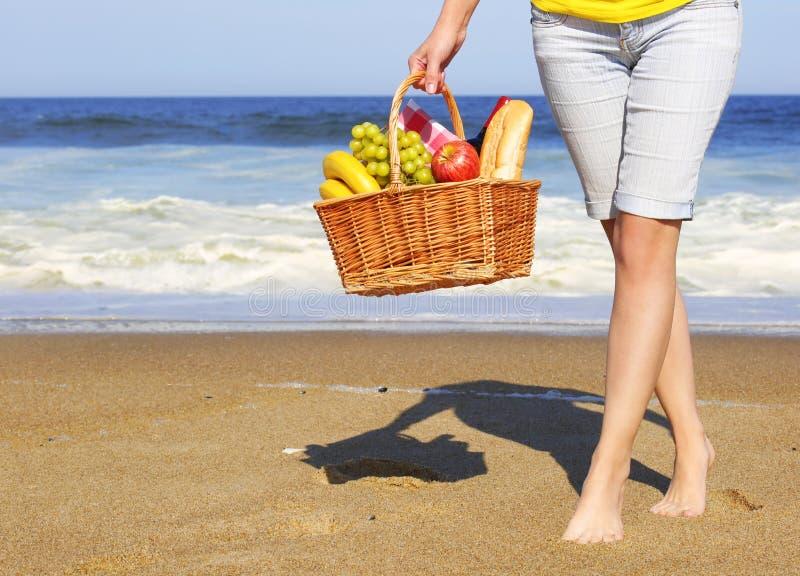 Piquenique na praia Pés e cesta fêmeas com alimento imagem de stock royalty free