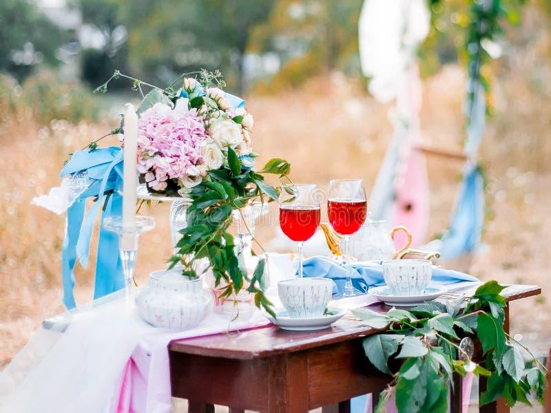 Piquenique para dois, vinho, chá, ramalhete das flores fotografia de stock royalty free
