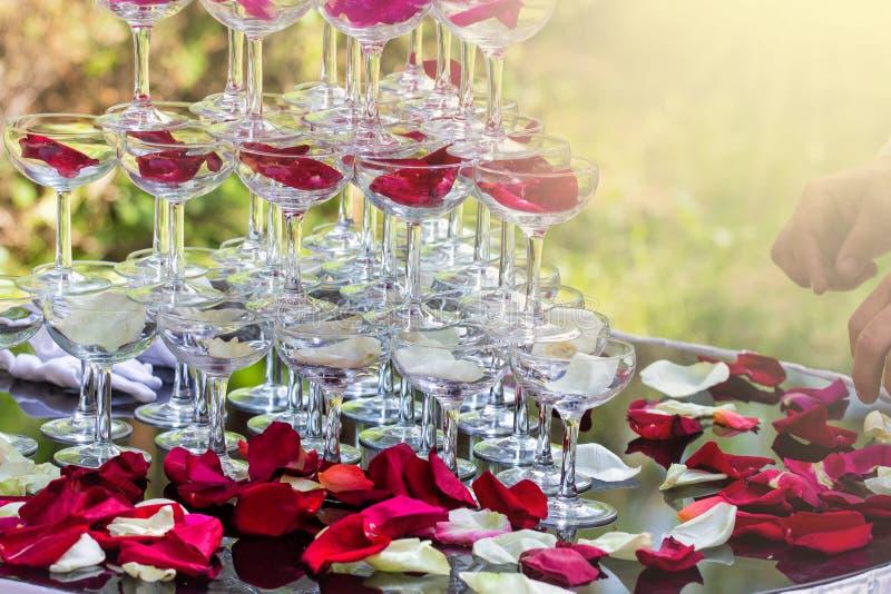 Pirámide con las copas de vino en una tabla adornada con los pétalos color de rosa en el restaurante Bebida agradable en el banqu fotografía de archivo