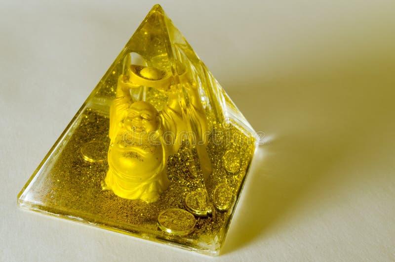 Pirámide con polvo y dinero de oro imagen de archivo