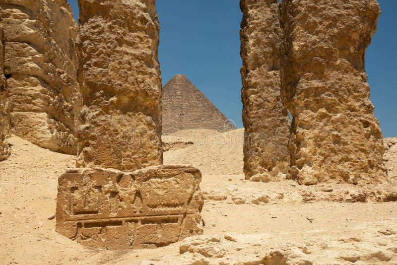 Pirámide de Khufu vista desde antiguas ruinas. Pilares y fragmento de piedra con jeroglíficos egipcios foto de archivo libre de regalías