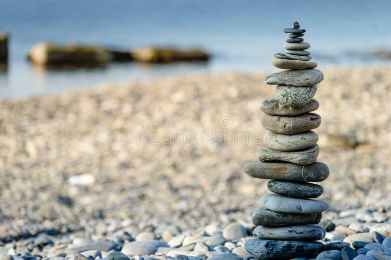 Pirámide de las piedras del mar en los guijarros de la orilla de mar El concepto de balanza y de espiritualidad fotos de archivo