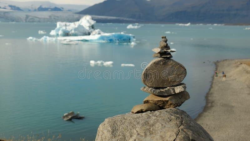 Pirámide de piedras contra la perspectiva de la laguna del glaciar del ³ n del rlà del ¡de Jökulsà imagen de archivo libre de regalías