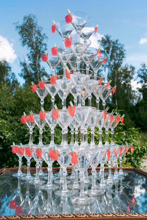 Pirámide de vidrios de champán en el jardín al aire libre en ceremonia de boda foto de archivo libre de regalías