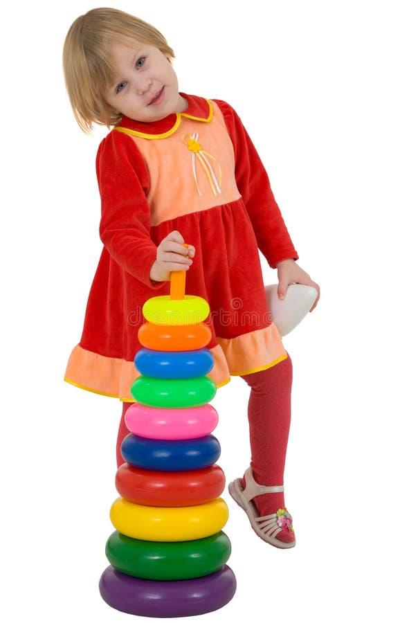 Pirámide del plástico de la niña y del juguete fotos de archivo