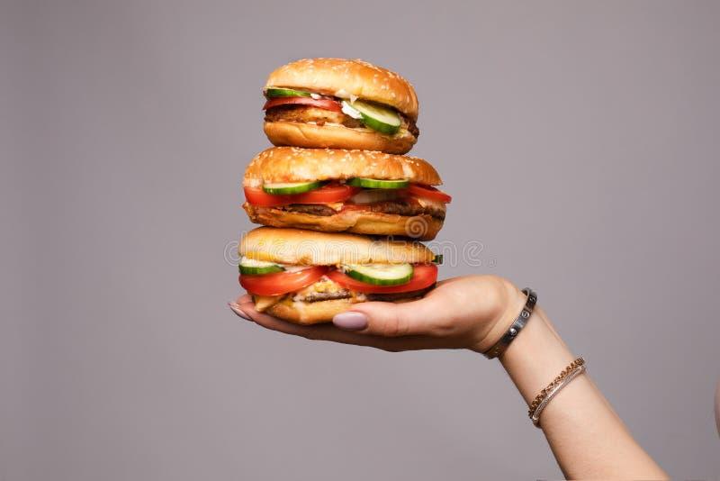 Pirámide femenina de la tenencia de la mano a partir de la hamburguesa apetitosa el tres aislada en el primer gris del fondo del  foto de archivo