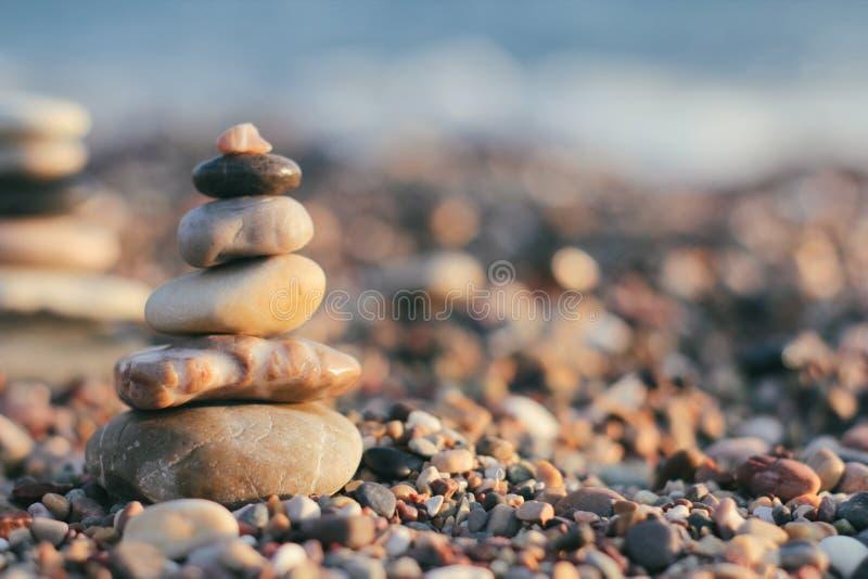 Pirámide zen de piedras balnearias en el fondo borroso del mar. Arena en la playa. Mar. Lugar del texto. Vistas al mar imagen de archivo