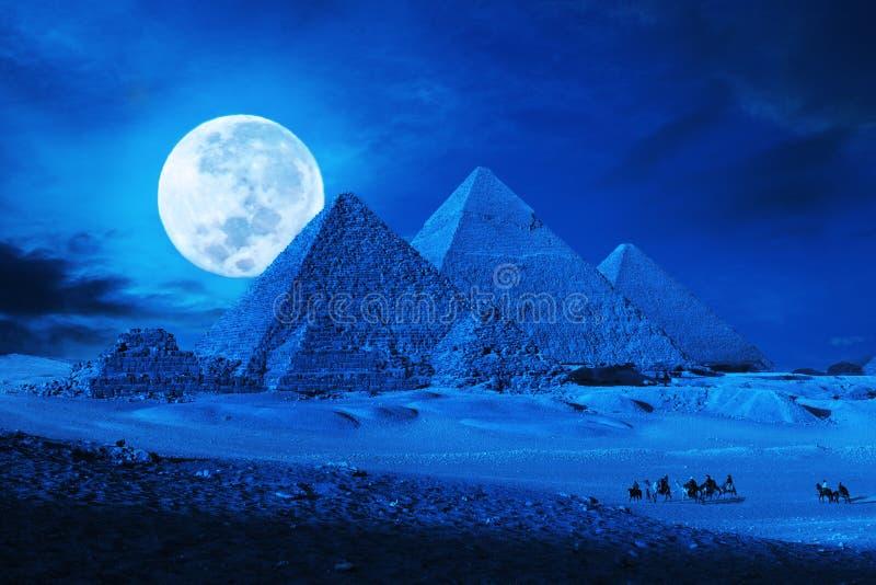 Pirámides Giza El Cairo Egipto con el tren del camello, caravane en la fantasía encendida de la noche de la Luna Llena fotografía de archivo libre de regalías