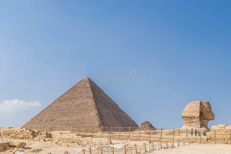 A pirâmide de Cheops e a cabeça da grande esfinge imagem de stock