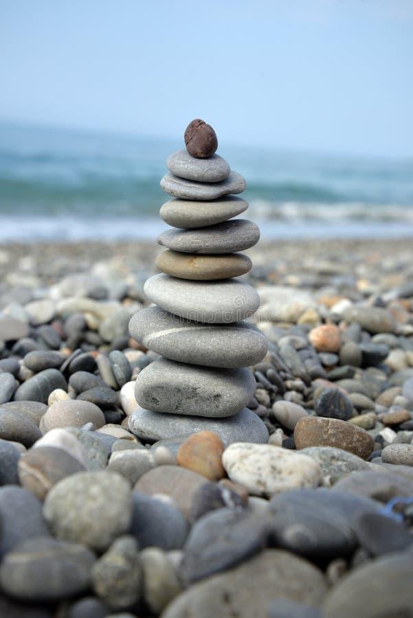 Pirâmide de pedra na costa de mar imagem de stock royalty free