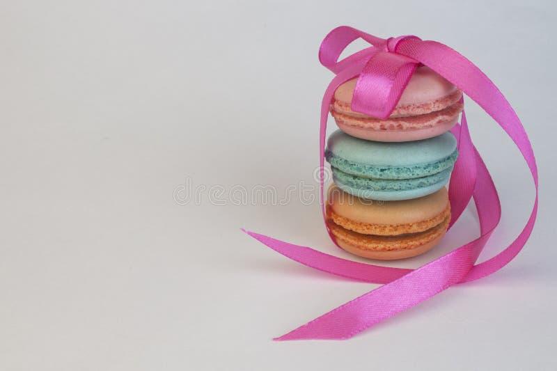 Pirâmide de 3 três macarons dos bolinhos de amêndoa amarrados com uma fita cor-de-rosa, sobremesa doce da decoração festiva, fund fotografia de stock royalty free