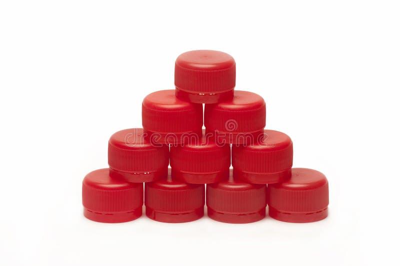 Pir?mide dos tamp?es de garrafa pl?sticos vermelhos isolados no fundo branco fotos de stock royalty free