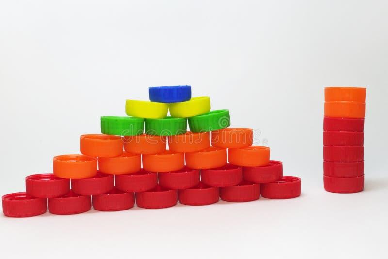 A pirâmide feita fora do plástico marcou tampões de garrafa e uma coluna de t fotos de stock royalty free