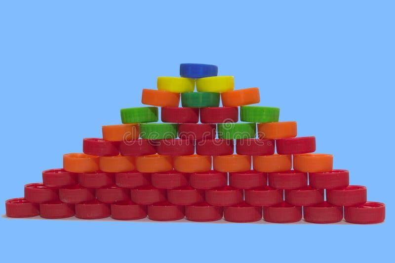 Pirâmide lisa de tampões de garrafa plásticos coloridos no backgrou azul foto de stock royalty free